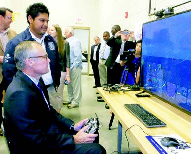 Putnam County High School Senior Jarad Coranado, standing, shows Georgia Lt. Gov. Casey Cagle how to operate a flight panel simulator.
