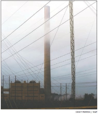 The 1,001-foot tall Plant Branch smokestack is partially obscured by clouds on the morning of its destruction.