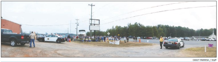 Scores of Putnam County residents gather near U.S. 441 and Lake Sinclair on the edge of a special restricted zone to watch the demolition of the Georgia Power smokestack on Saturday.
